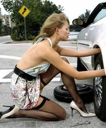 девушка чинит авто колесо
